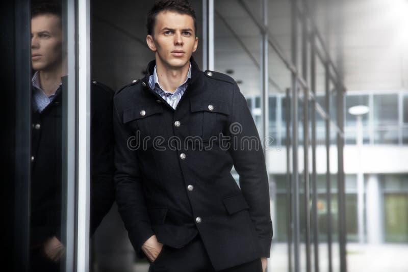 Dana mannen med dräkten som poserar på det moderna kontoret arkivbilder