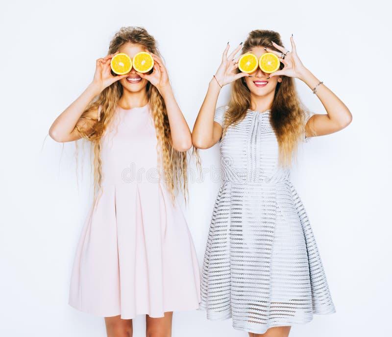 Dana och skönhet Två bedöva skönhetflickor som har gyckel med skivor av apelsiner som stänger vid dem ögon royaltyfri fotografi