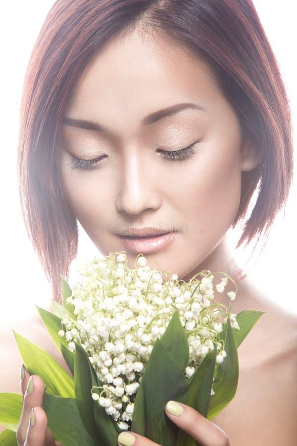 Dana orientalisk typ för den härliga flickan med delikat naturligt smink och blommor Härlig le flicka fotografering för bildbyråer