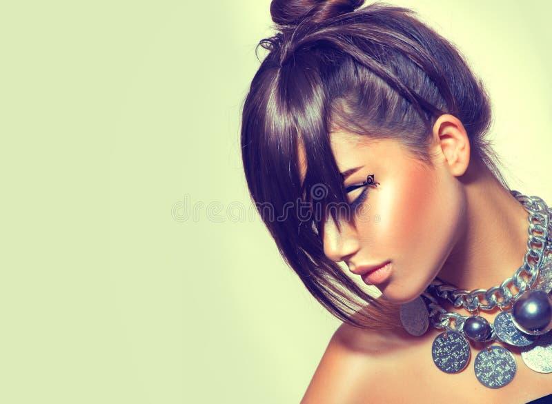 Dana skönhetflickan Ursnygg brunettkvinnastående Stilfull fransfrisyr och makeup royaltyfri bild