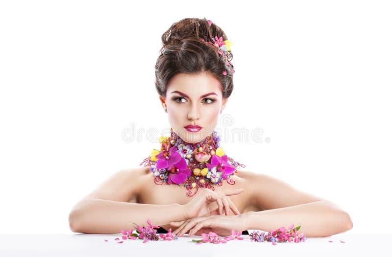 Dana skönhetkvinnan med blommor i hennes hår och runt om hennes hals Perfekt idérik smink- och hårstil royaltyfri fotografi