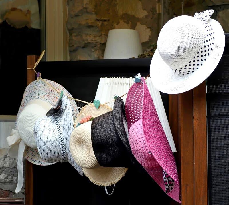 Dana sommarsugrörhattar för kvinna som hänger på ett rep utanför en shoppa royaltyfria foton