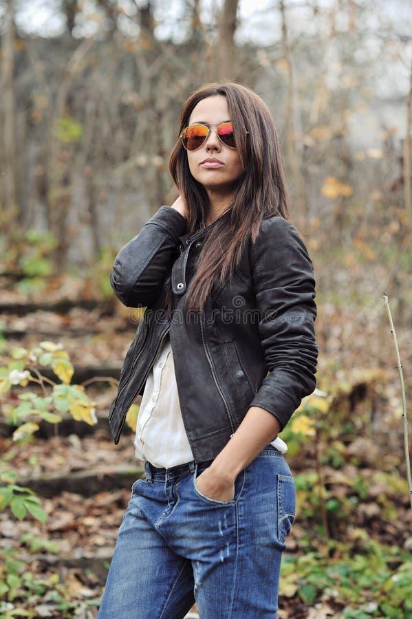 Dana ståenden av attraktiv bärande jeans för den unga kvinnan, omslag arkivbild