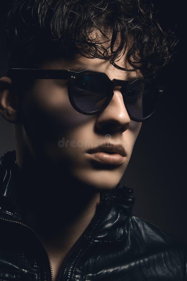 Dana ståenden av den sexiga unga mannen med solglasögon mot mörker arkivfoton
