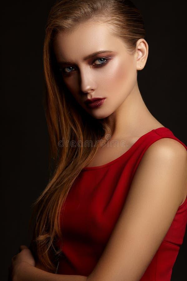 Dana ståenden av den unga attraktiva flickan i röd klänning arkivfoton