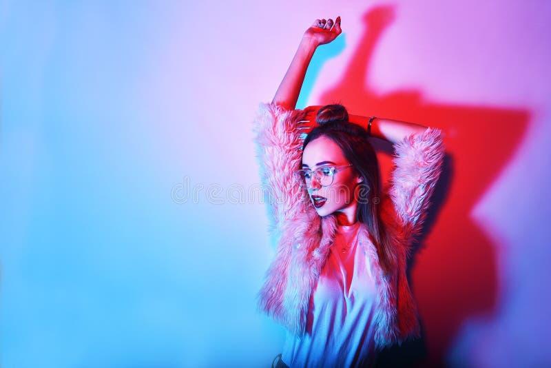 Dana ståenden av den unga eleganta flickan i exponeringsglas Kulör bakgrund, studioskott Härlig brunettkvinna hipsterflickadans arkivbild