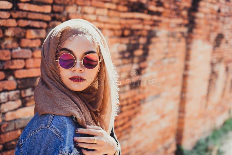 Dana ståenden av den unga härliga muslimkvinnan och den gamla tegelstenväggen royaltyfria bilder