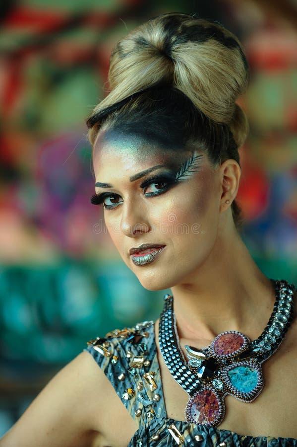 Dana ståenden av den unga kvinnan med idérikt smink och frisyren royaltyfri fotografi