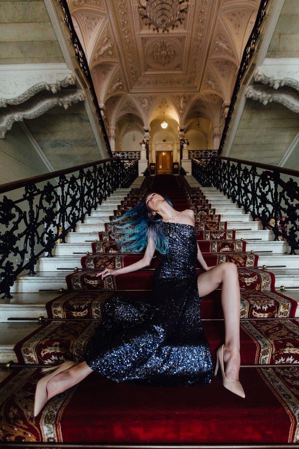 Dana ståenden av den ursnygga flickan med blått färgat hår länge Den härliga aftoncoctailklänningen arkivbild