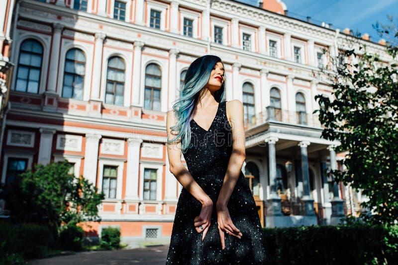 Dana ståenden av den ursnygga flickan med blått färgat hår länge Den härliga aftoncoctailklänningen arkivfoton