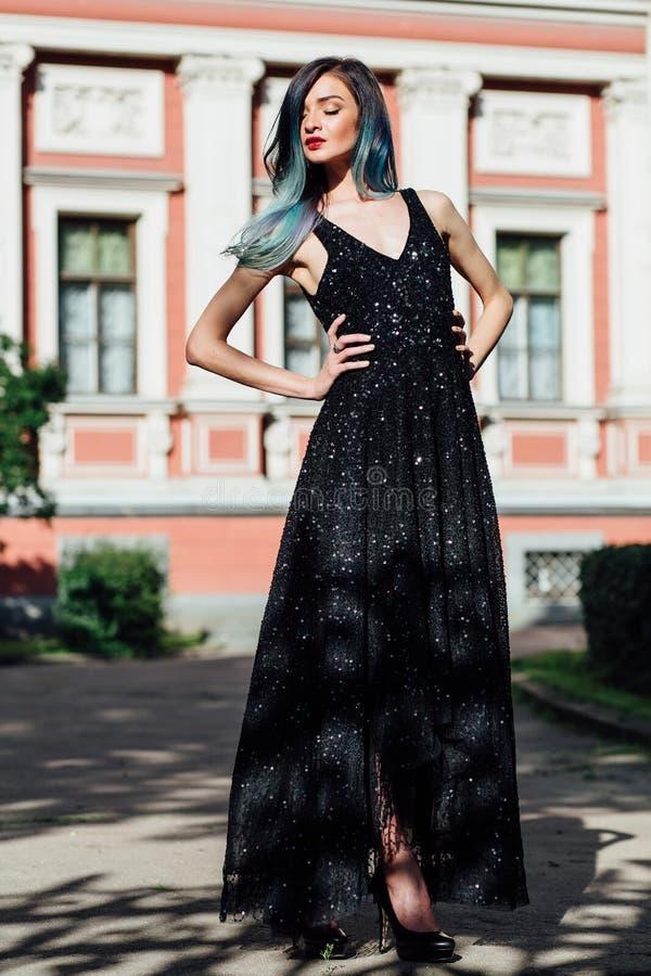 Dana ståenden av den ursnygga flickan med blått färgat hår länge Den härliga aftoncoctailklänningen royaltyfri foto