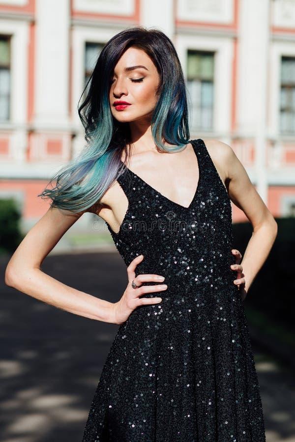 Dana ståenden av den ursnygga flickan med blått färgat hår länge Den härliga aftoncoctailklänningen royaltyfria bilder
