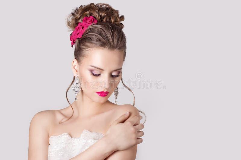 Dana ståenden av en härlig attraktiv flicka med höga försiktiga eleganta frisyrer för ett aftonbröllop och ljust smink med flöde fotografering för bildbyråer