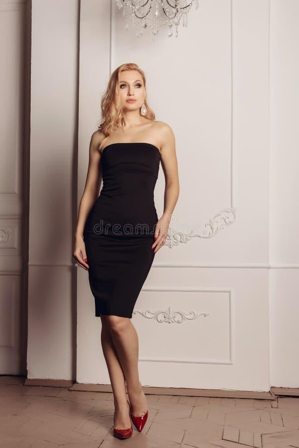 Dana ståenden av en kvinna i en härlig aftonklänning Den lyxiga inre, gör perfekt diagram- och hårflickan arkivbild