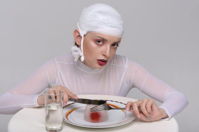 Dana ståenden av en sjuk flicka med en förbinda på hennes huvud arkivfoto