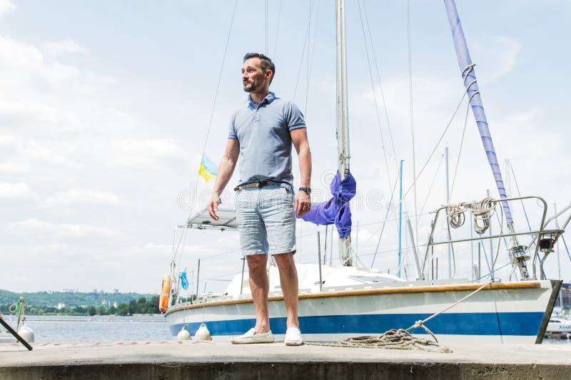 Dana ståenden för den unga mannen på floden och yachter på bakgrund sjöman med yachten Manståenden mot yachter med vikt seglar royaltyfri fotografi