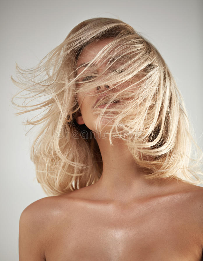 Dana stilståenden av en blondin med tilltrasslat hår royaltyfria foton