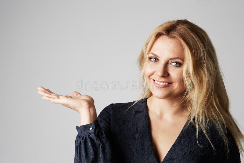 Dana tätt upp fotoet av en härlig blond kvinna i en nätt klänning som poserar med handen över grå tom bakgrund arkivbilder