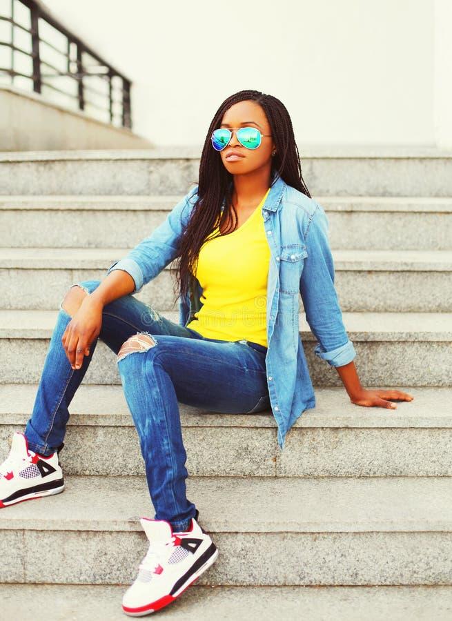 Dana ungt afrikanskt bära för kvinna solglasögon- och jeansskjortasammanträde på trappa i stad royaltyfri fotografi