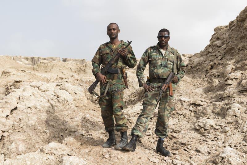 Danakil, Эфиопия, 22-ое января 2015: 2 солдата представляя гордо с их оружи в горах соли пустыни Danakil стоковые изображения