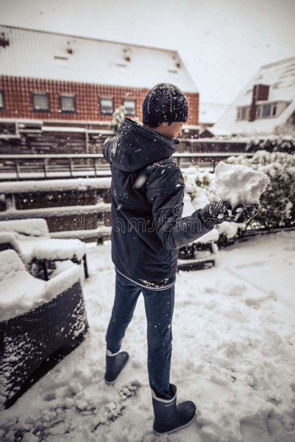 Danande kastar snöboll i en trädgård royaltyfria foton