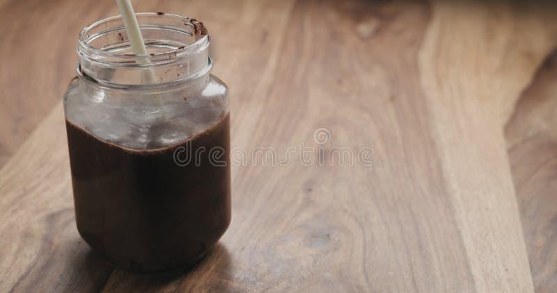 Danandekakaodrinken i den glass kruset med handtaget på den wood tabellen, mjölkar häller arkivbild