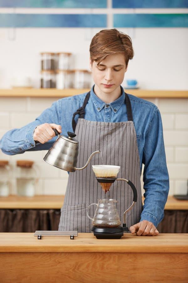 Danandepouroverkaffe Trevlig barista som förbereder kaffedrinken som ser koncentrerad royaltyfria foton