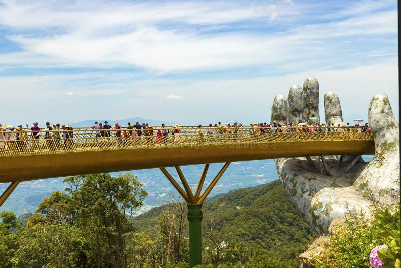 Danang Vietnam - JUNI, 24, 2019: Den guld- bron i den Bana dalen som stöttas av en jätte- hand denna bro, är 1 400 meter fotografering för bildbyråer