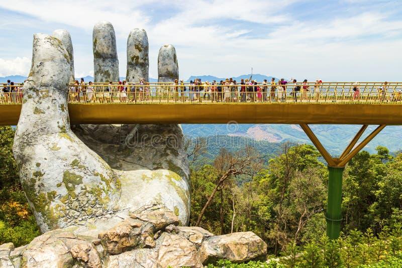 Danang, Vietnam - JUNIO, 24, 2019: El puente de oro en el valle de Bana, apoyado por una mano gigante este puente es 1.400 metros foto de archivo