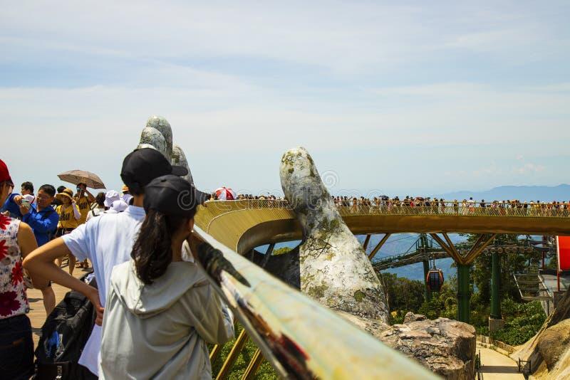 Danang, Vietname - 24 de junho de 2019: A ponte dourada é levantada por duas mãos gigantes na estância turística no monte do Na d fotos de stock