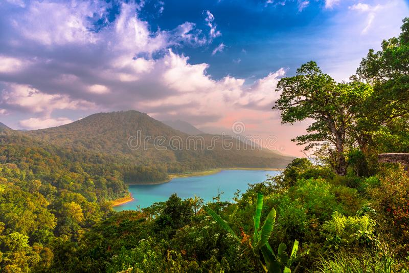 Danau Buyan Lake surrounded by green forests and vegetation at sunset under a cloudy blue sky in Bali, Indonesia, Asia. Danau Buyan Lake surrounded by green stock photos
