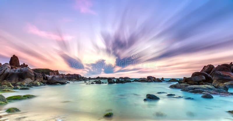 Dance of cloudy dawn on coastal reefs royalty free stock photo