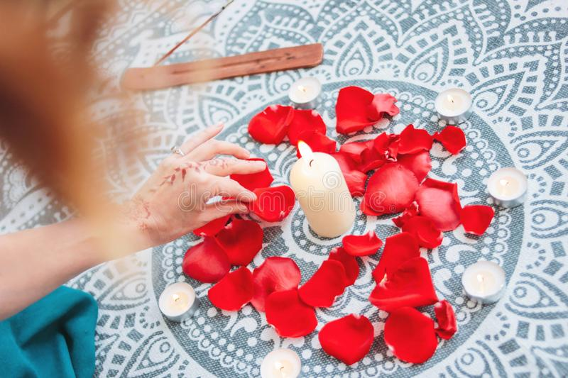 Dance of female hands with mehendi over the altar of candles and rose petals, women practices stock photo