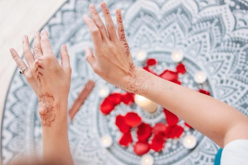 Dance of female hands with mehendi over the altar of candles and rose petals, women practices. Dance of female hands with mehendi over the altar of candles and royalty free stock images