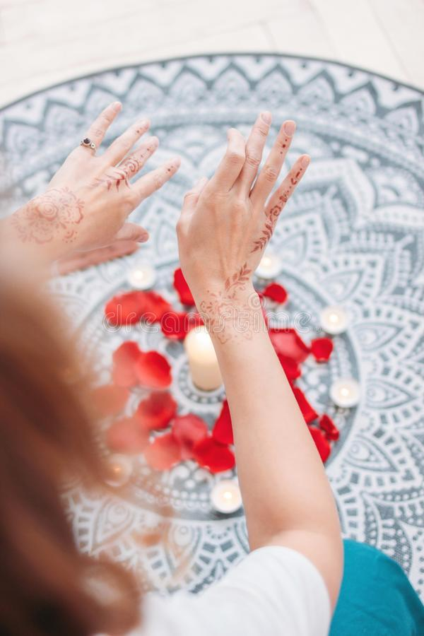 Dance of female hands with mehendi over the altar of candles and rose petals, women practices. Dance of female hands with mehendi over the altar of candles and stock photos