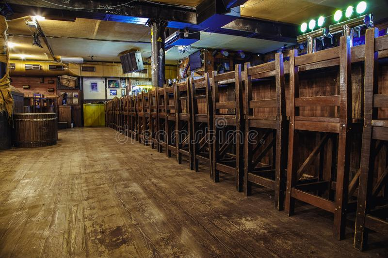 Dance floor in beer pub. Kiev, Ukraine- March 19, 2018. wooden tall chairs lined up along a bar counter in an Irish pub pub. behind the chairs is a dance floor royalty free stock images