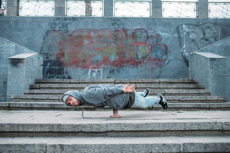 Dance performer stands on one hand, street dancing. Modern dancing style. Male dancer, cityscape on background royalty free stock photo