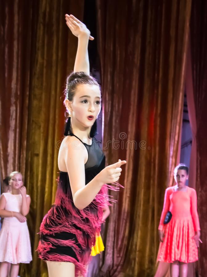 Dance school. Pupils take exams. Boys and girls in beautiful dance costumes on stage royalty free stock images