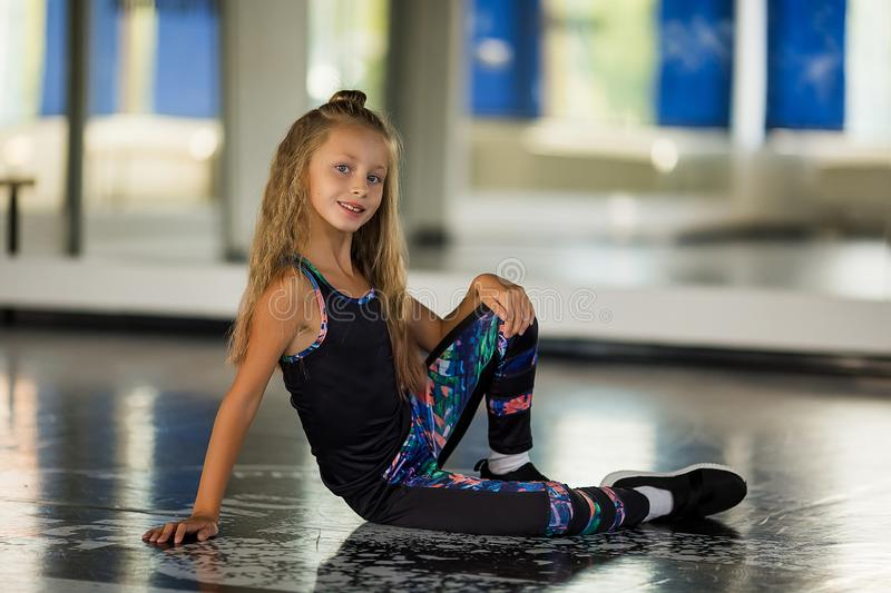 Dance styles street dancers, hip hop. Flexible body. Girl in a dance studio in a suit royalty free stock photo