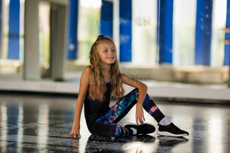 Dance styles street dancers, hip hop. Girl in a dance studio in a suit. Dance styles street dancers, hip hop. Flexible body. Girl in a dance studio in a suit royalty free stock image