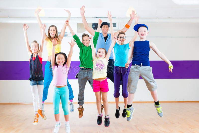 Dance teacher giving kids Zumba fitness class. Dance teacher giving children Zumba fitness class in gym stock photos