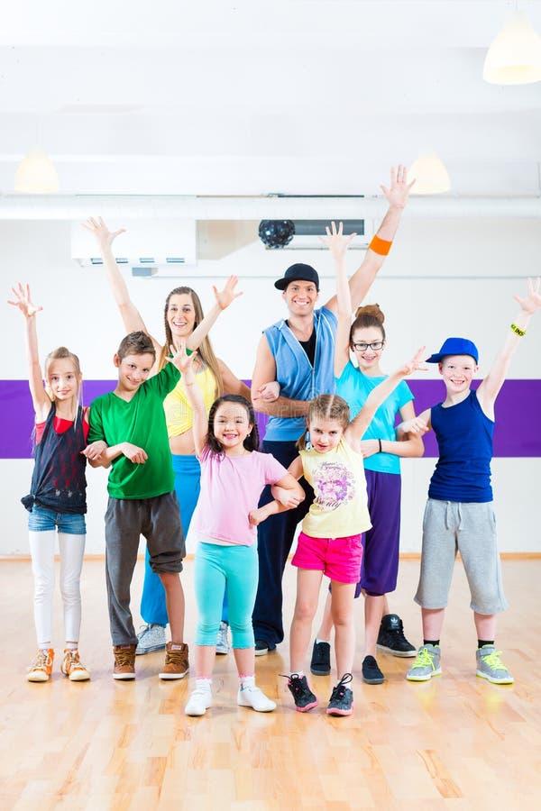 Dance teacher giving kids Zumba fitness class. Dance teacher giving children Zumba fitness class in gym stock photo
