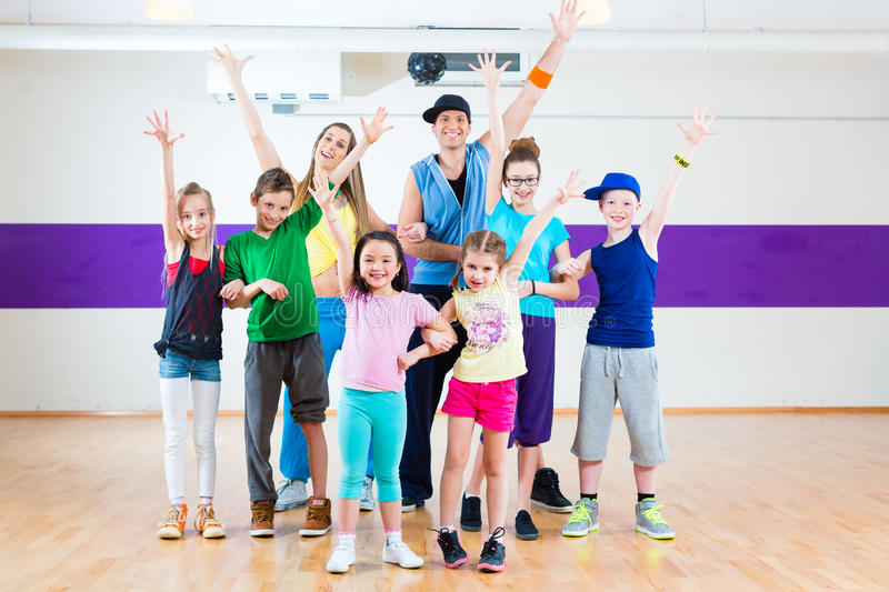 Dance teacher giving kids Zumba fitness class. Dance teacher giving children Zumba fitness class in gym stock images