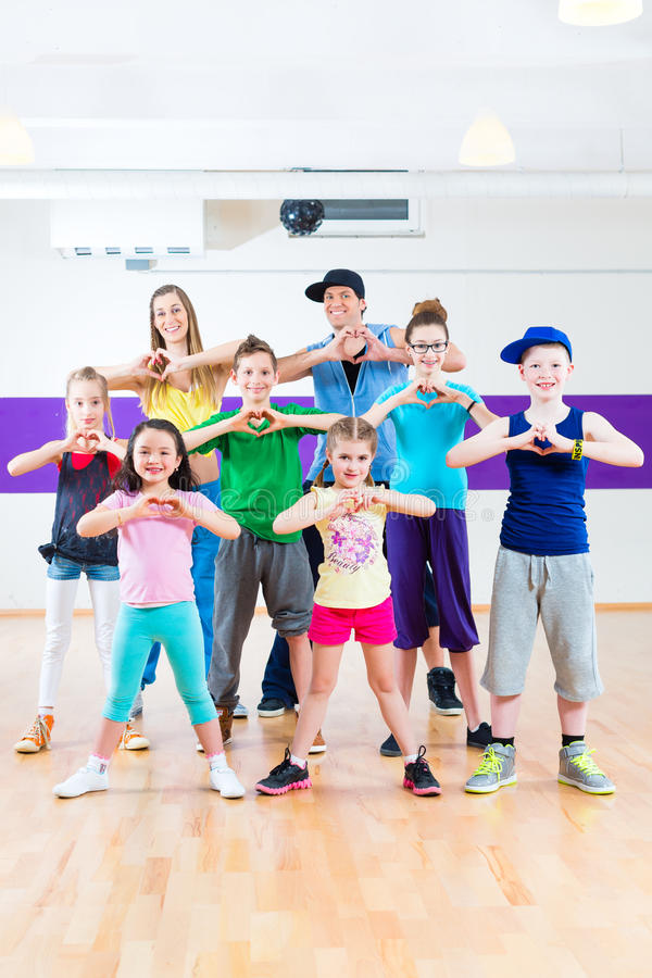 Dance teacher giving kids Zumba fitness class. Dance teacher giving children Zumba fitness class in gym royalty free stock image