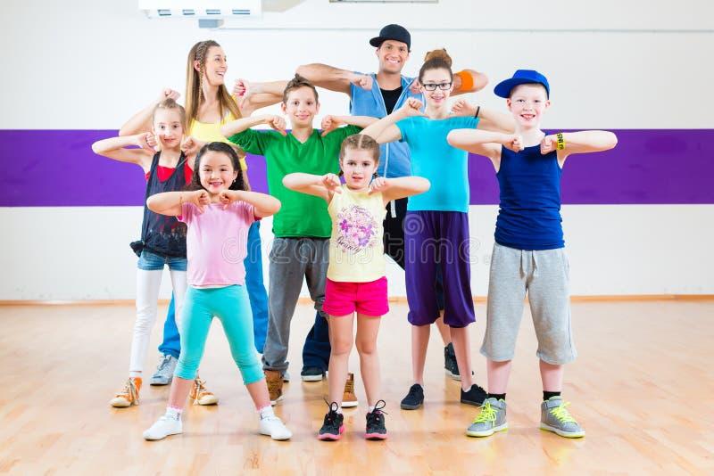 Dance teacher giving kids Zumba fitness class. Dance teacher giving children Zumba fitness class in gym royalty free stock photos