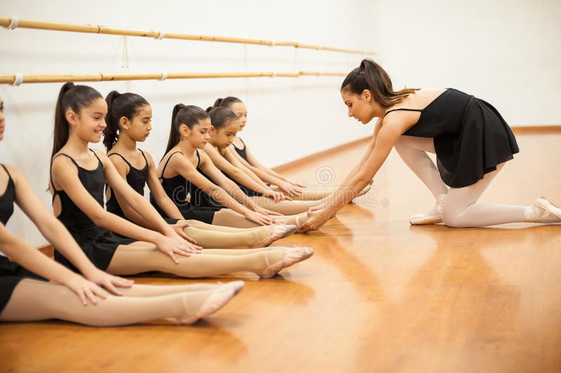 Dance teacher helping students with posture stock images