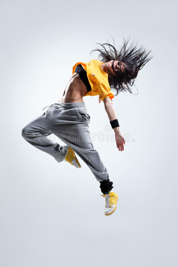 The dancer. Modern style dancer jumping on studio background stock photo