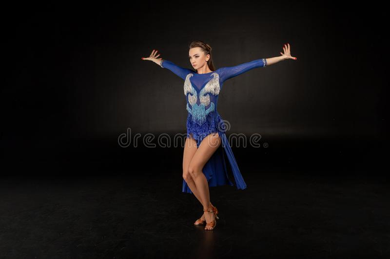 Dancer in blue dress is dancing in the dark studio royalty free stock images
