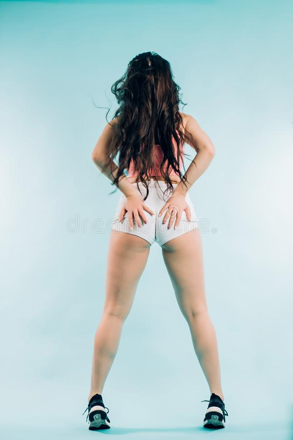 Dancer brunette woman with a beautiful figure in short shorts and long hair stands backwards on a blue background royalty free stock images