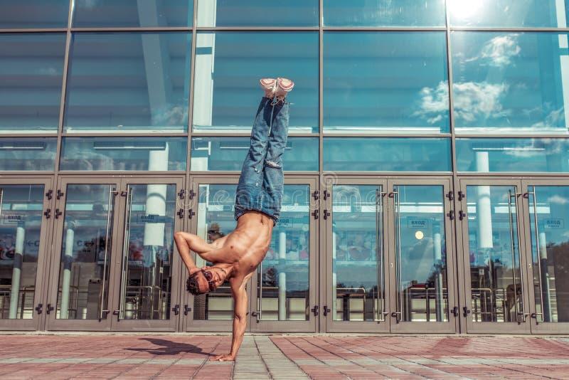 Dancer dans le saut debout sur un bras, acrobate acteur break dance, hip-hop En été, des vitraux d'arrière-plan nuisent photo libre de droits